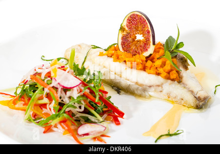 Baked fish with salad on a white background in restaurant - Stock Photo