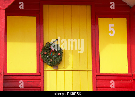 festive wreath hanging on the door of a bright yellow and red beach hut at Swanage in December - Stock Photo