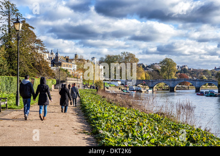 A couple holding hands and people walking on the path next to the river Thames towards Richmond bridge - Stock Photo