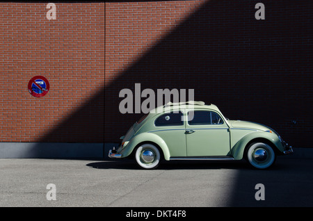A classic Volkswagen Beetle is parked next to a No Parking sign. - Stock Photo