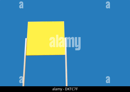 yellow clear signboard against blue background with copy space - Stock Photo