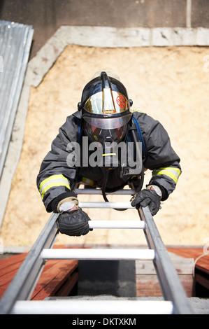 Firefighter climb on fire metal stairs - Stock Photo