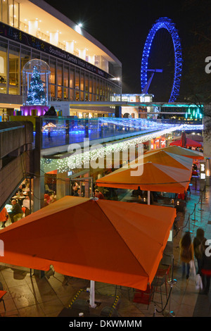 Christmas decorations at the Southbank Centre Royal Festival Hall with illuminated London Eye beyond England UK - Stock Photo