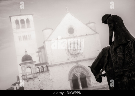Morning fog creates a moody backdrop for this statue of a knight on horseback in front of the Basilica of St. Francis - Stock Photo