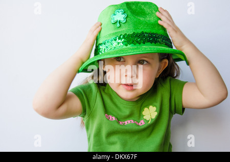 Pretty little girl tries on a hat for St. Patrick's Day - Stock Photo