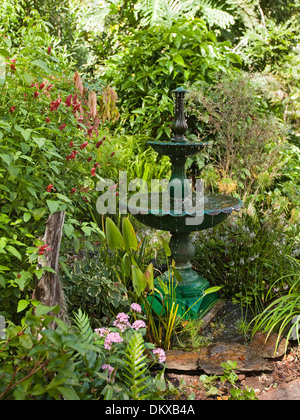 Spectacular lush sub-tropical garden with decorative fountain water feature, emerald foliage, flowering shrubs and - Stock Photo