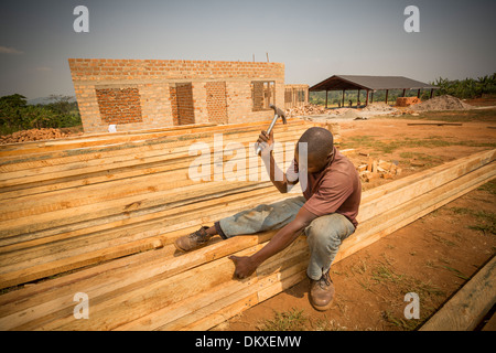 Construction workers build a new warehouse on the outskirts of Kampala, Uganda, East Africa. - Stock Photo