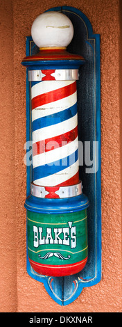 Old fashioned barber's pole outside a barber shop on First Street in historic downtown Fort Myers, Florida, USA - Stock Photo