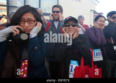 Feb 28, 2010 - Los Angeles, California, USA - Spectators block their ears to block the noise of exploding firecrackers - Stock Photo
