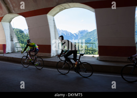 Cyclists ride over a covered bridge during the Maratona dles Dolomites race in Italy, 2013 - Stock Photo