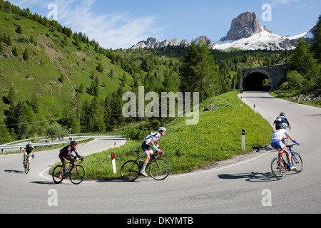 Pack of cyclists ride by a mountain during the Maratona dles Dolomites race in Italy, 2013 - Stock Photo