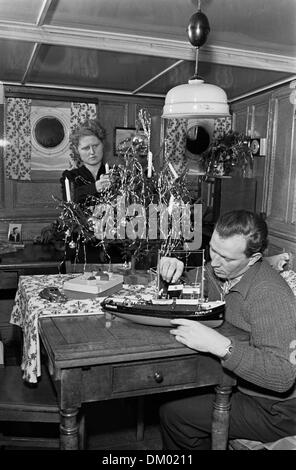A man does handicrafts on a ship model, a woman decorates a small Christmas tree in the background, undated photograph - Stock Photo