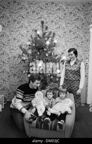 A family with two children with dolls is pictured in front of a decorated Christmas tree in a living room in Dresden, - Stock Photo