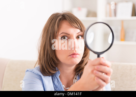 Beautiful woman holding loupe or magnifying glass inher hand - Stock Photo