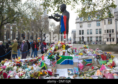 London, UK 10th December 2013. Tributes are paid to Nelson Mandela where his statue is situated on Parliament Square, - Stock Photo