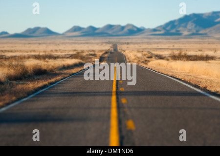 A long road through the desert in Arizona at sunset - Stock Photo