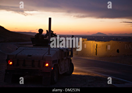 A US Marine provides security from a humvee during a convoy outside Forward Operating Base Zeebrugge at dusk December - Stock Photo