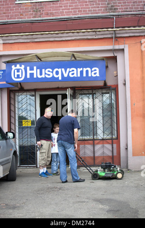 Customers picking up repaired lawnmower at the Husqvarna shop. Tomaszow Mazowiecki Central Poland - Stock Photo