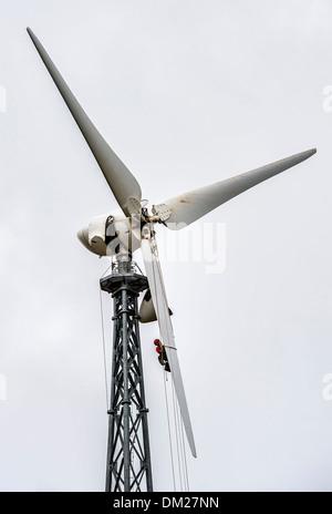 Man repairing the propeller of a wind turbine.