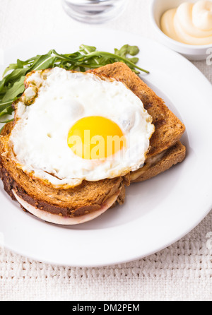 Croque Madame - sandwich with ham, cheese and fried egg - Stock Photo