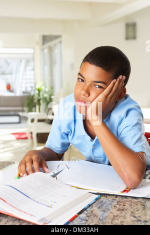 Fed Up Boy Doing Homework In Kitchen - Stock Photo