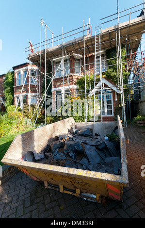 Old slates in a skip as the roof is replaced on a south London period home. - Stock Photo