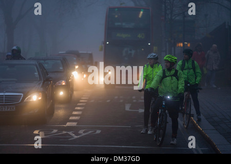Commuting cyclists wait to cross a junction at dawn on a foggy morning in south London. - Stock Photo