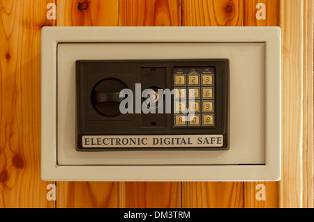 Dusty Electronic strong box on wooden wall. - Stock Photo