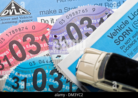 British car tax discs and child's toy car England UK United Kingdom GB Great Britain - Stock Photo