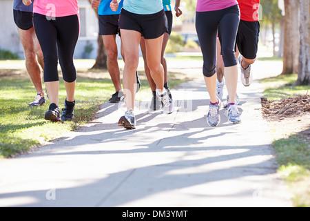 Close Up Of Runners Feet On Suburban Street - Stock Photo