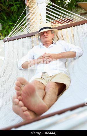 Senior Man Relaxing In Beach Hammock - Stock Photo