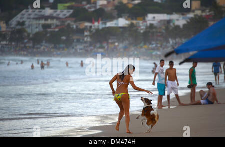 Natal, Brazil. 7th Dec, 2013. A young woman runs with a dog along the beach of Ponta Negro in Natal, Brazil, 7 December - Stock Photo