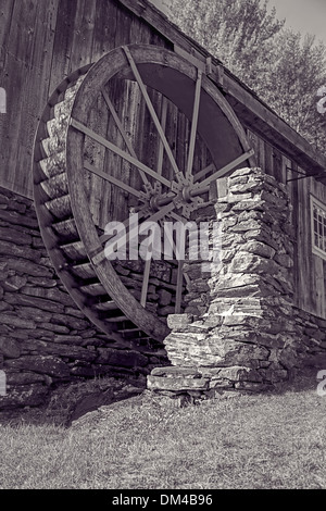 An old grist mill with water wheel in black and white. - Stock Photo