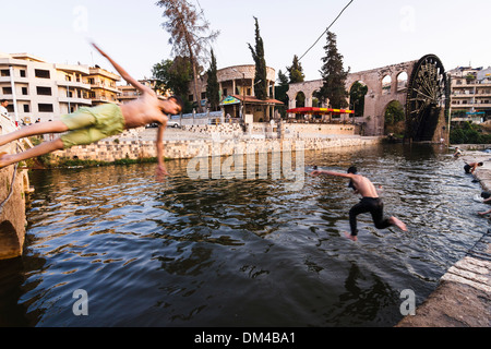 Teens jumping on the water at the pool of Al Mohammediyya Noria, the largest of the Hama water wheels. Hama, Syria - Stock Photo