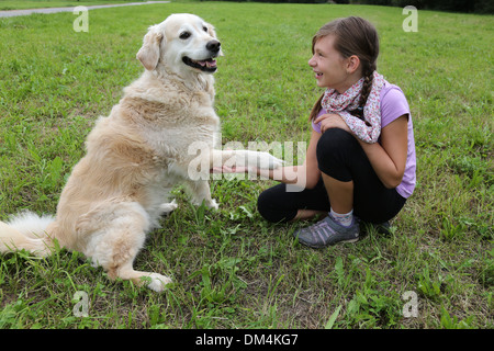 A dog is shaking hands with a young girl on a meadow - Stock Photo