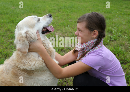 Little girl fondling a dog on a meadow - Stock Photo