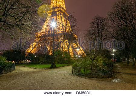 The base of the Eiffel Tower at night in the Parc du Champ de Mars, Paris, Île-de-France, France, Europe - Stock Photo