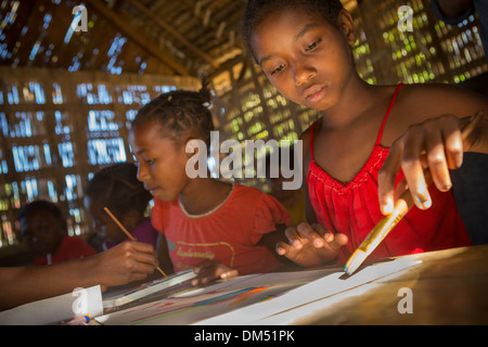 Children painting in art class in Vatomandry District, Madagascar. - Stock Photo