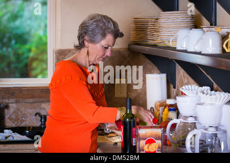 Mature woman, Caucasian, 59 years old, is preparing snacks in her kitchen for an outdoor party. - Stock Photo