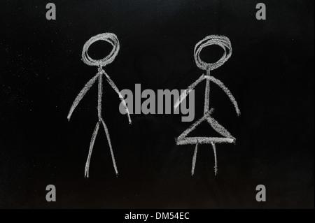 Man and woman stick people drawn on a blackboard in chalk. - Stock Photo