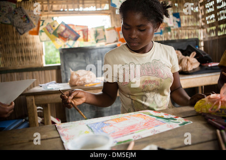 A child paints in art class in Vatomandry District, Madagascar. - Stock Photo