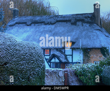 Black and white, timber-framed thatched cottage in winter, Mickleton near Chipping Campden, Gloucestershire, England. - Stock Photo