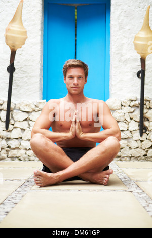 Man Meditating Outdoors At Health Spa - Stock Photo