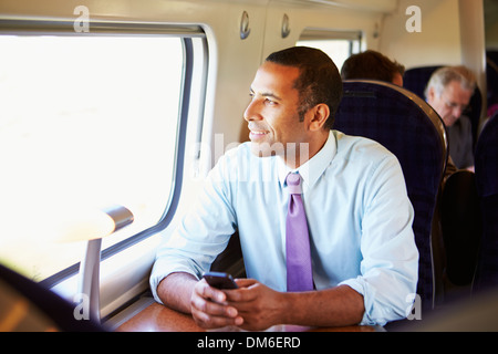 Businessman Commuting To Work On Train Using Mobile Phone - Stock Photo