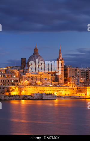 Malta, Valletta, skyline with St. Paul's Anglican Cathedral and Carmelite Church at dusk from Sliema - Stock Photo