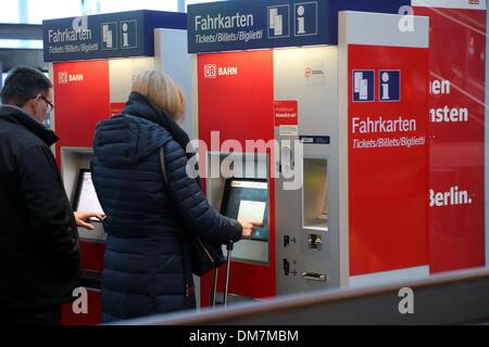 Berlin, Germany. 12th Dec, 2013. Passengers buy tickets at a ticket machine of German railway company Deutsche Bahn - Stock Photo