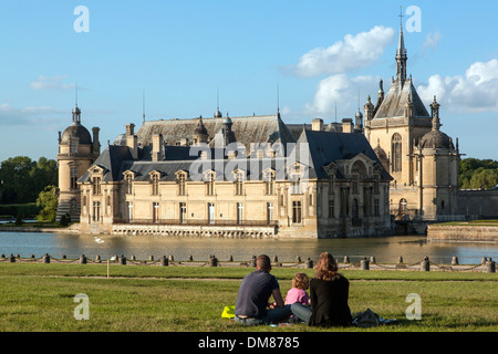 FAMILY SITTING ON THE LAWN ACROSS FROM THE CHATEAU DE CHANTILLY AND ITS MOAT, OISE (60), FRANCE - Stock Photo