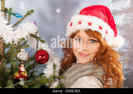 Portrait of woman in winter with snow and Christmas tree - Stock Photo