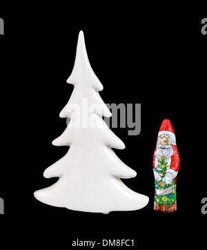 Chocolate figure of santa Claus and Christmas tree isolated over black background with clipping path. - Stock Photo