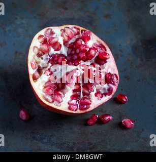 Half a pomegranate on a dark grey rustic surface - Stock Photo